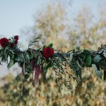 Deep red flowers on wedding arch